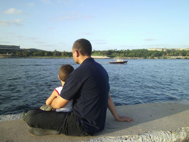 Un abrazo de padre e hijo en el malecón de La Habana